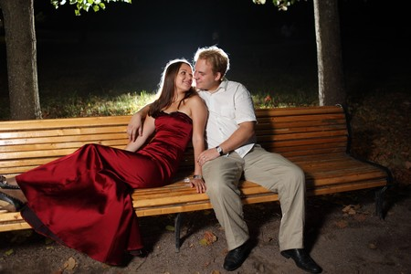 Young couple sitting together on park bench at night.