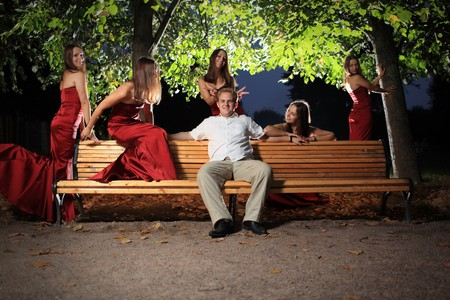 surrounded: Happy young man on bench in night park, surrounded by sexy woman in red dress. Stock Photo