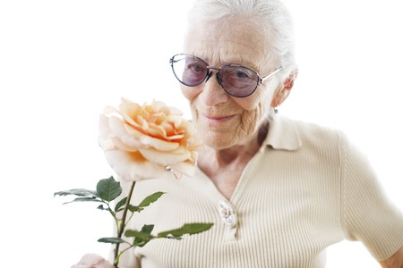 Happy senior woman with rose flower over white background. Close-up, shallow DOF. photo