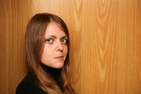 skepticism: Portrait of young woman over wooden wall looking at camera