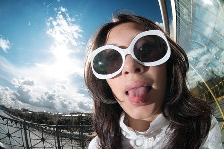 Fun portrait of young woman in funky sunglasses sticking her tongue out photo