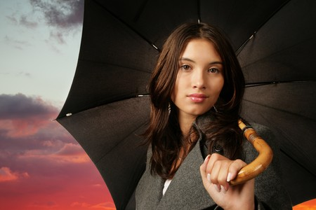 Beautiful Asian woman with umbrella over dramaric sunset sky background. photo