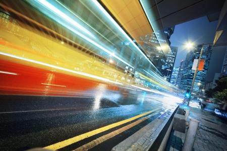 Long exposure shot of blurred bus speeding through night street.