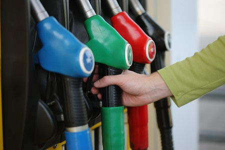 benzine: Closeup of male hand holding gas pump nozzle at gas station.