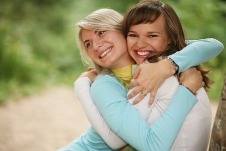 Closeup portrait of two happy female friends hugging outdoors in park. Shallow DOF.