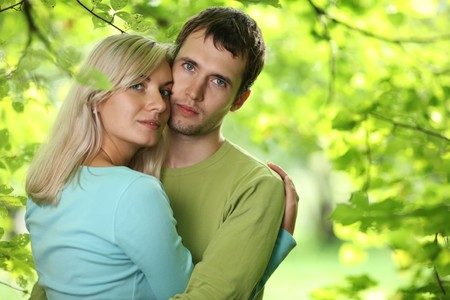 Closeup portrait of young couple in love outdoors, hugging over green foliage background. Shallow DOF. photo