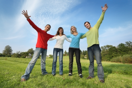 raise hand: Group of four happy friends together outdoors on green field.