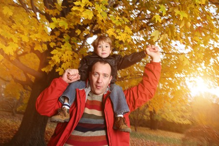 shoulder ride: Portrait of happy father giving son piggyback ride on his shoulders in autumn park.
