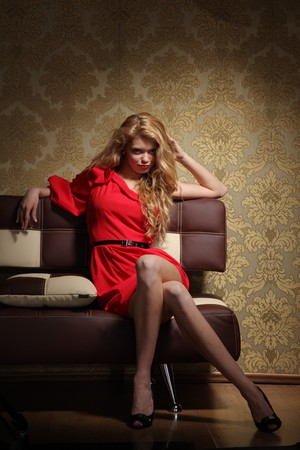 Beautiful blond glamour woman in red dress sitting on sofa in luxury retro interior