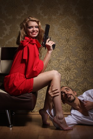 Sexy young adult woman with handgun sitting over man lying on floor and begging for mercy. photo