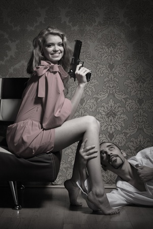 breakup: Sexy young adult woman with handgun sitting over man lying on floor and begging for mercy.
