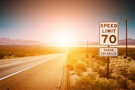 arizona sunset: Highway road to sunset. 70 MPH speed limit sign. Stock Photo