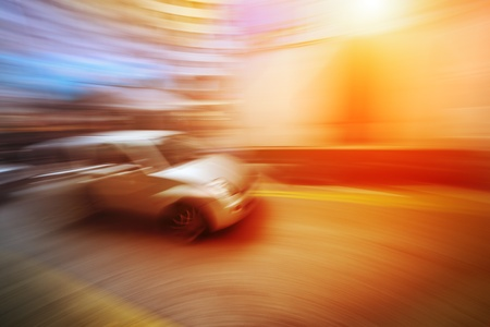 Long exposure shot of car moving in blurred motion on bright colorful background. Intentionally blurred.