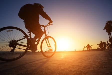 Biker silhouet rijdend langs het strand bij zons ondergang