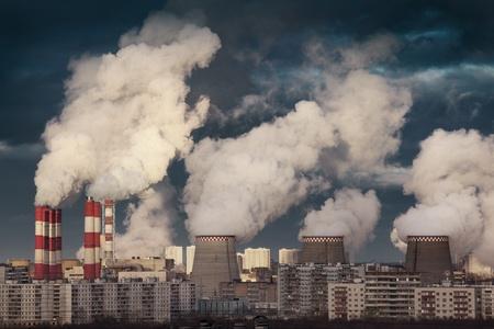 smokestacks: Power plant smokestacks emitting smoke over urban cityscape Stock Photo