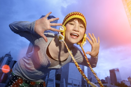 excitement: Outdoor portrait of happy young Asian woman in trendy knitted hat with palms open. Twilight city and blue sky as background.
