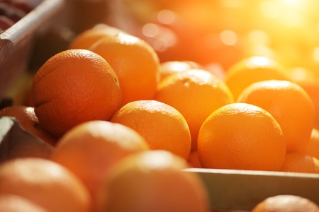 Fresh organic oranges on display on sunny day. Shallow DOF. Stock Photo