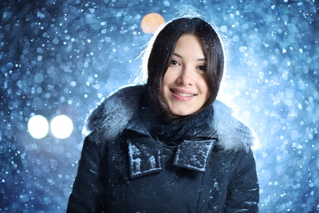 Closeup portrait of happy smiling young female in winter clothes over falling snow background at night. photo