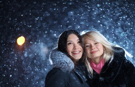 Two happy young female friends enjoying snowfall on Christmas winter night. Archivio Fotografico