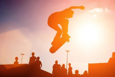 Jumping skateboarder silhouette over sunset sky background