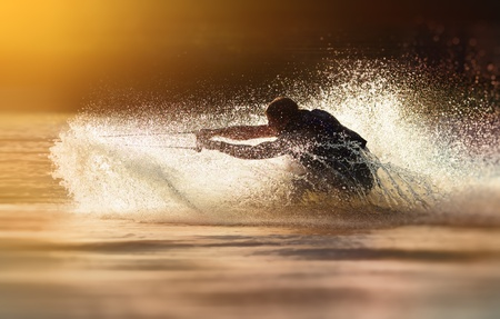 wakeboarding: Waterskier silhouette moving fast in splashes of water at sunset