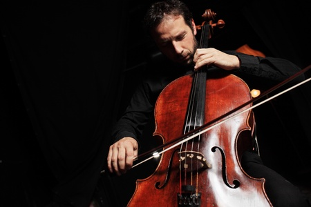 musician: Portrait of cellist playing classical music on cello on black background. Copyspace.