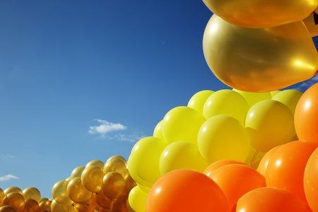 Bright colorful inflatable balloons up in air over blue sky background. photo