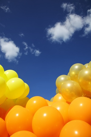 multiple: Bright colorful inflatable balloons up in air over blue sky background.