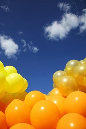 Heldere kleurrijke opblaasbare ballonnen omhoog in de lucht over blauwe hemelachtergrond.