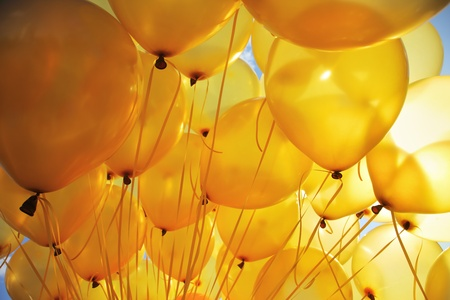 objects: Background of  bright yellow inflatable balloons up in the air, backlit by sun.