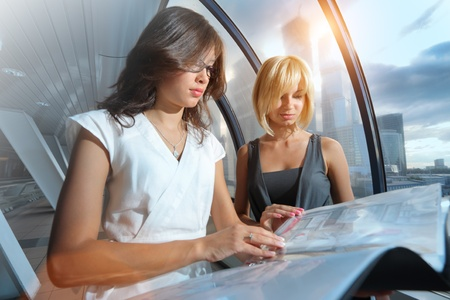 futuristic girl: Two businesswomen looking into papers in futuristic interior Stock Photo