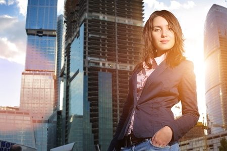 Young businesswoman over construction site with modern office buildings photo