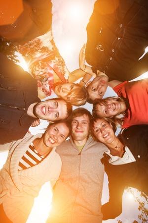 Groep van gelukkige jonge mensen in cirkel buitenshuis