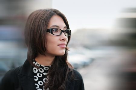 Portrait of beautiful young businesswoman outdoor over blurred street background. Closeup, shallow DOF. Stock fotó