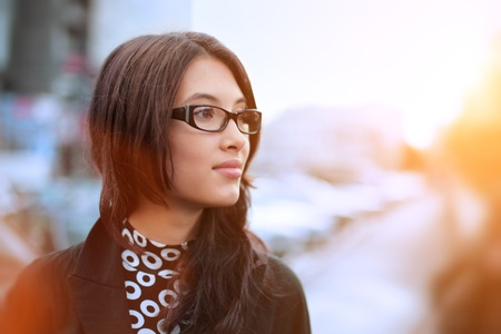 Portrait of beautiful young businesswoman outdoor over blurred street background. Closeup, shallow DOF. photo