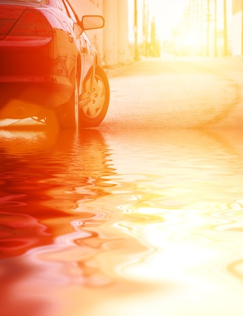 reflects: Red car reflects in water on sunny street, closeup on bumper.