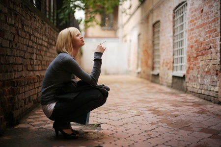 Portrait of young woman smoking cigarette in old city street background. Copyspace, shallow DOF.