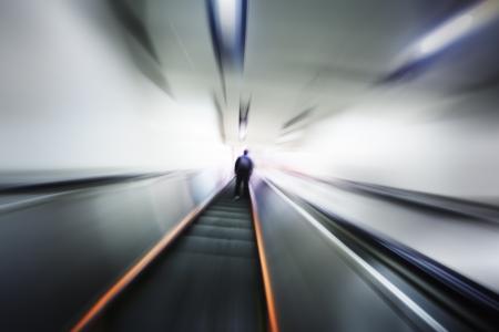 외로운 사람 에스 컬 레이터 계단을 위로 이동합니다. 흐려진 모션 관점.