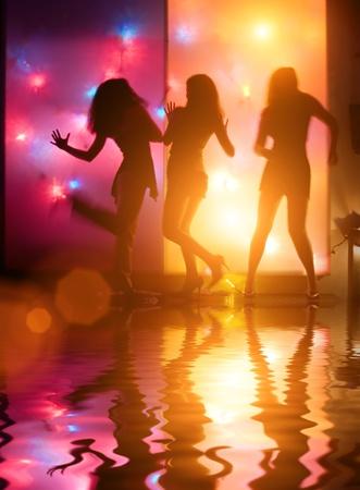 chicas bailando: Baile de siluetas de las ni�as en frente de coloridas luces disco Foto de archivo