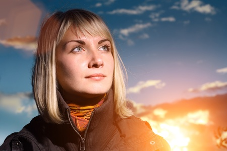 Beautiful blond girl over blue sky at sunset photo