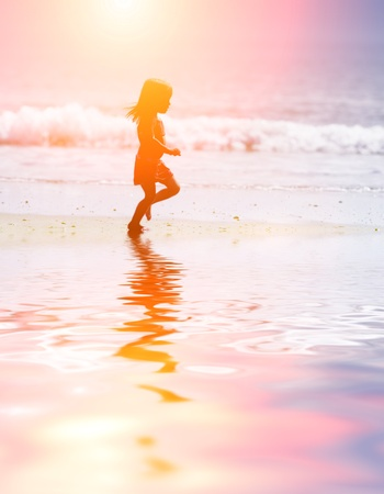 Child running on water at ocean beach at sunset.