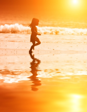 Happy little girl running at ocean beach at scenic sunset. photo