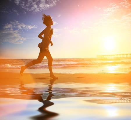 people jogging: Mujer que se ejecuta en la playa del oc�ano al atardecer
