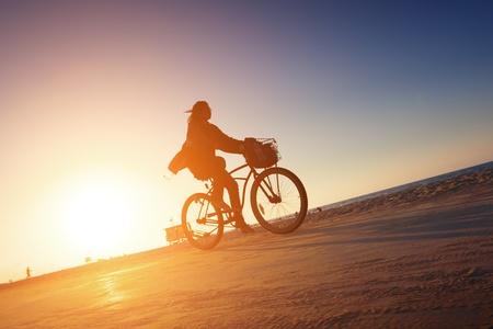 bicyclist: Biker silhouette riding along beach at sunset Stock Photo