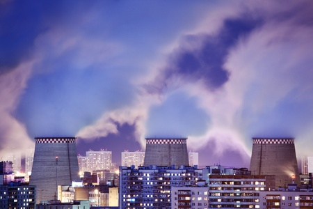 smokestacks: Power plant smokestacks emitting smoke over night cityscape