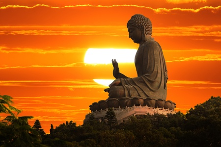 Buddha statue over scenic sunset sky background Reklamní fotografie