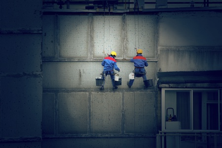 harness: Painters in hard hats and harnesses hanging high on concrete wall, working.