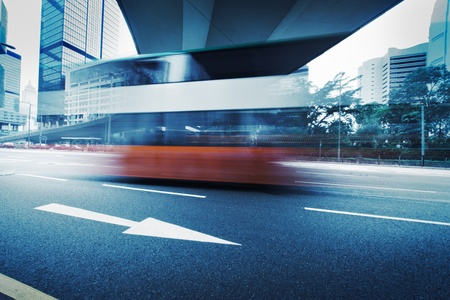Long exposure photo of bus moving on urban road. Motion blur over city background. Cross processed colors. Stock Photo