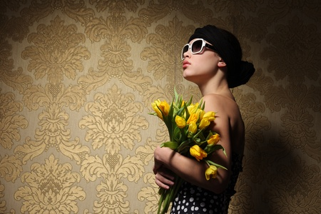 Retro looking young woman in kerchief with yellow flowers looking up against vintage golden wallpaper background. Copyspace. photo