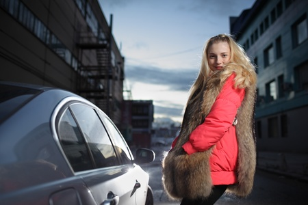 winter fashion: Portrait of beautiful young blond woman in fur vest standing next to her new car in city street at twilight.